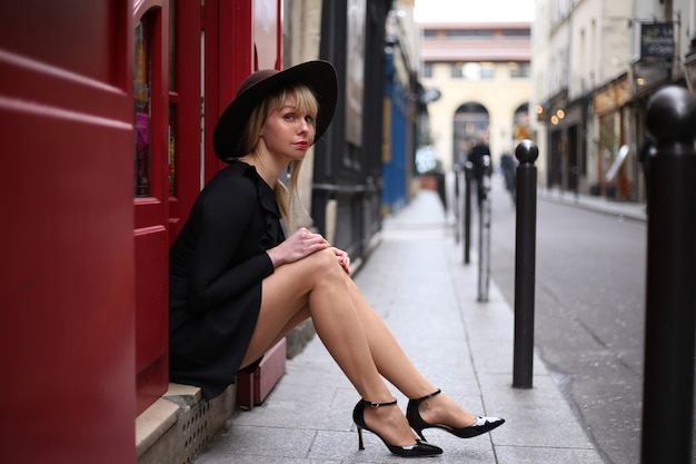 赤いドアの近くの通りに一人で座っている短い黒のドレスで美しい脚の長いブロンド