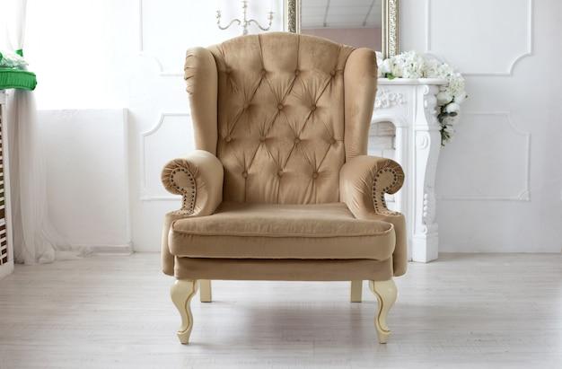 Мягкое бежевое винтажное кресло стоит в центре белой комнаты.