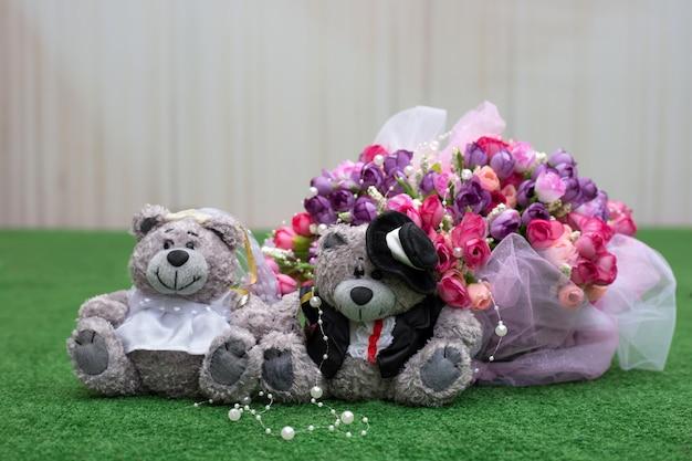 Молодожены тедди возле свадебного букета на зеленой траве. свадебная композиция