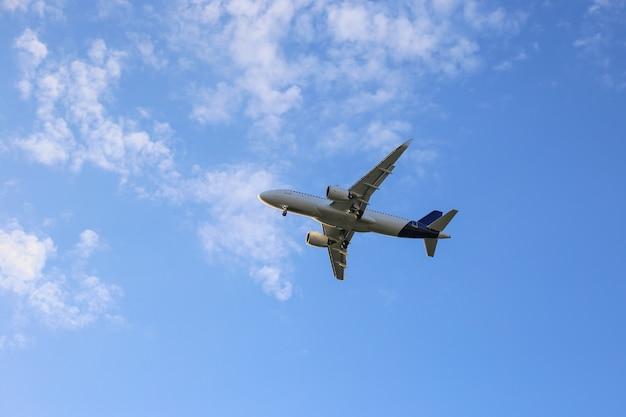 白い雲と青い空を飛んでいる大きな白い飛行機。