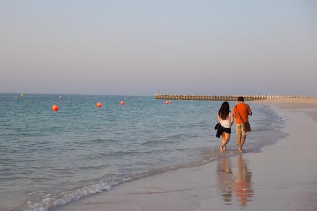 若いカップルは、夕暮れ時のドバイのビーチに沿って歩きます。夏のロマンス