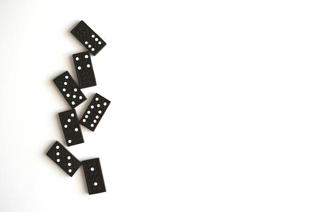 Черные домино лежат на белом фоне, вид сверху. настольная игра. место для текста