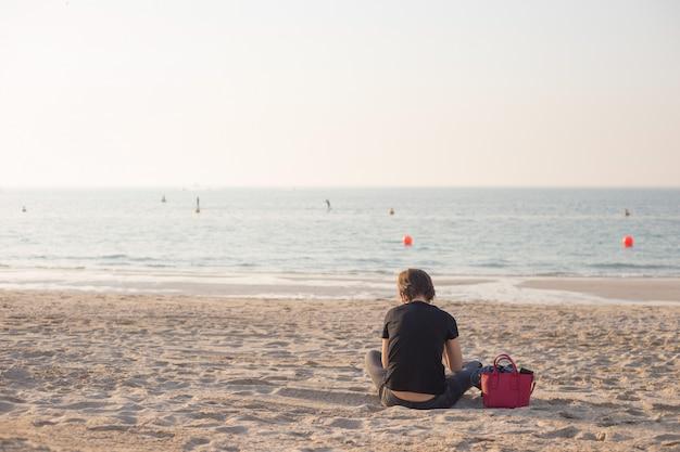 Безликая женщина с красной сумкой читает в одиночестве на пляже. понятие одиночества