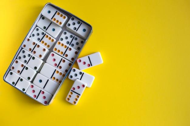 Игра домино в коробке металла на желтой предпосылке, взгляд сверху. семейная настольная игра
