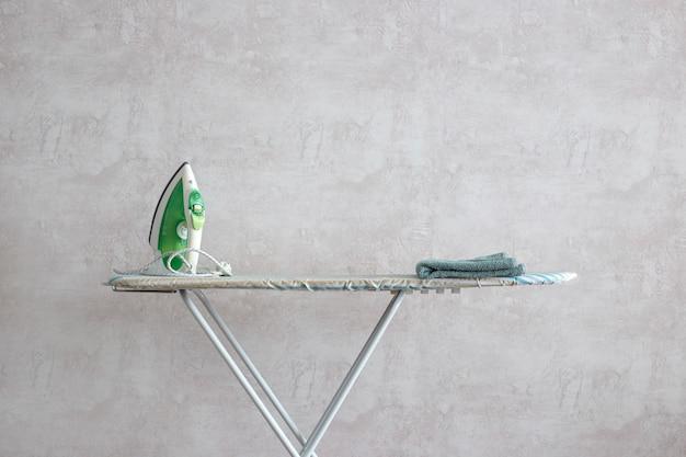 Зеленый утюг стоит на гладильной доске.