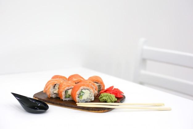 Филадельфия катится с лососем в суши-баре на белом столе рядом с палочками для еды