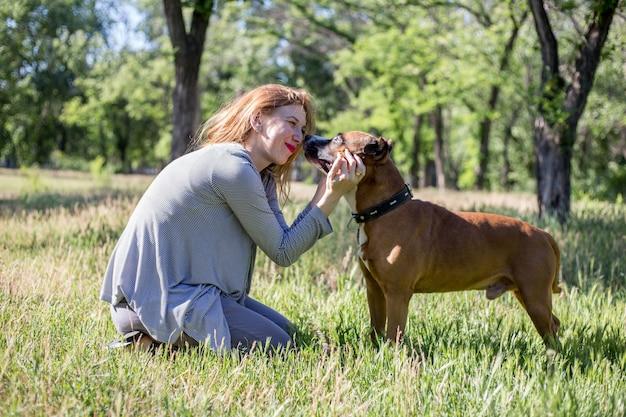 赤い髪の少女は晴れた日に公園で犬と遊んでいます。
