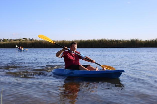 Мужчина летом плывет по реке на каяке