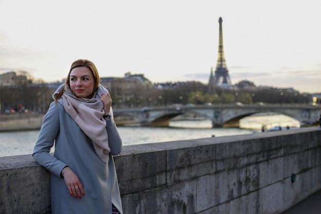 秋のパリの川とエッフェル塔の近くに一人で立つ女性