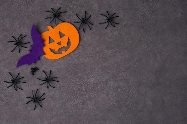 Вид сверху джек-о-фонарь и летучая мышь из войлока рядом с пауками на коричневом фоне