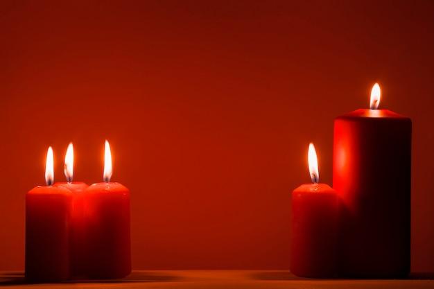 Красные горящие свечи на красной предпосылке.