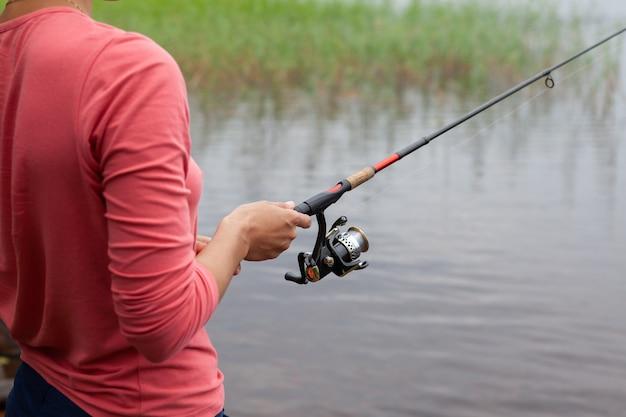 女性の手で釣りリールと釣り竿