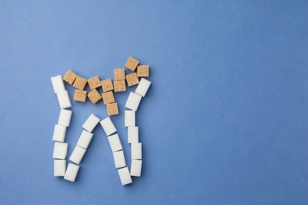 青色の背景に砂糖で作られた白いブロッケン歯。口腔衛生の概念。