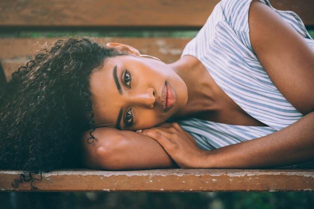 Красивая молодая черная женщина, лежа на стуле в парке