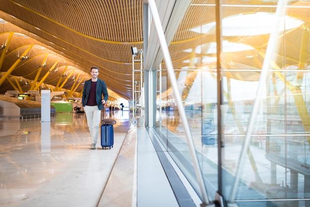 Прогулка человека в аэропорту с помощью мобильного телефона