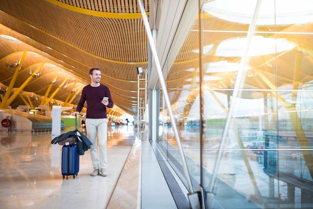 携帯電話を使用して空港で歩いている男の前部