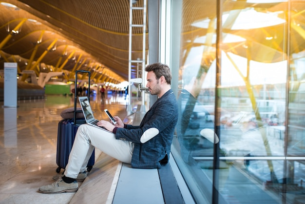 Человек сидит в аэропорту с помощью ноутбука и мобильного телефона рядом с окном