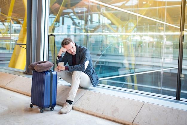 彼の飛行が遅れている空港で動揺し、悲しいと怒っている男