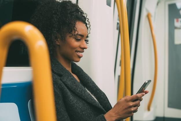 Счастливая молодая негритянка сидит в метро на мобильном телефоне