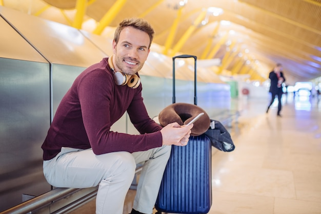 Молодой человек ждет прослушивания музыки и с помощью мобильного телефона в аэропорту с чемоданом.