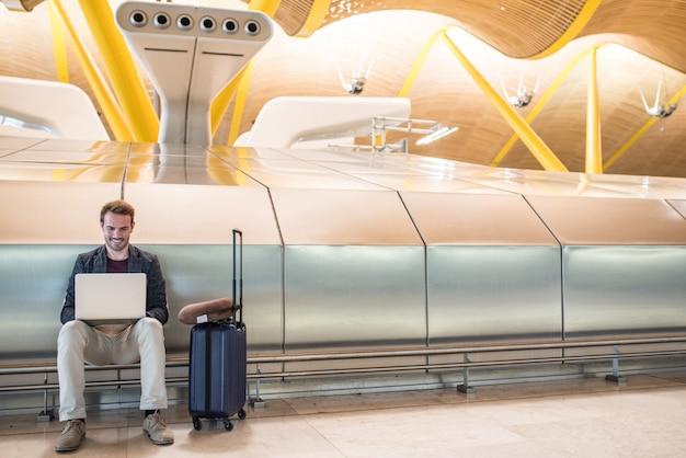 Молодой привлекательный мужчина, сидя в аэропорту, работает с ноутбуком, ожидая его полета с чемоданом