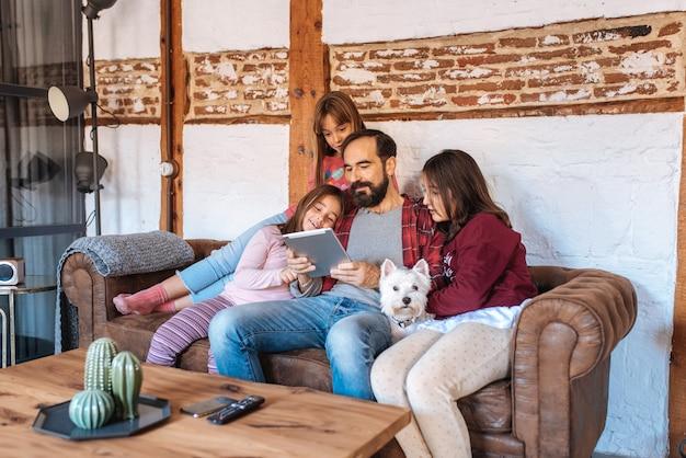 Счастливый папа со своими дочерьми смотрит на планшет дома сидя на диване с собакой