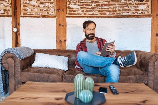 Человек сидел на диване расслабленной дома на столе