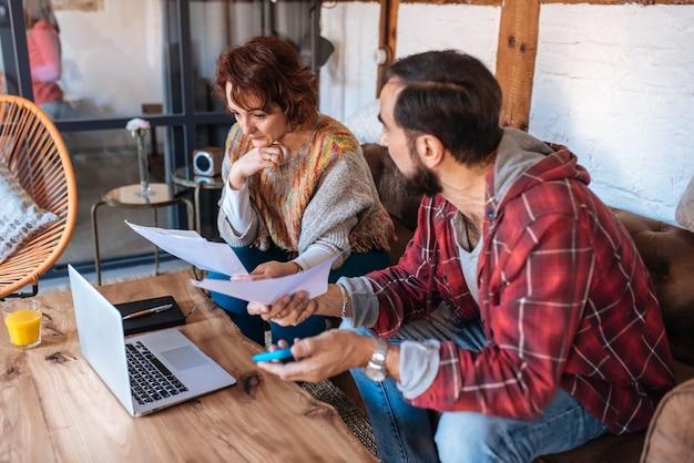 Пожилая пара сидит дома, глядя на свои проблемы с финансами