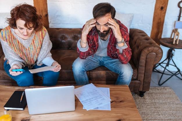 彼らの財政問題を見て家に座っている成熟したカップル