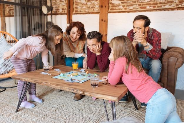 古典的なテーブルゲームをプレイしてソファで自宅で幸せな家族