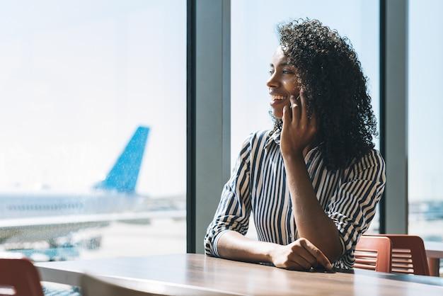Женщина на мобильном телефоне ждет своего рейса в аэропорту