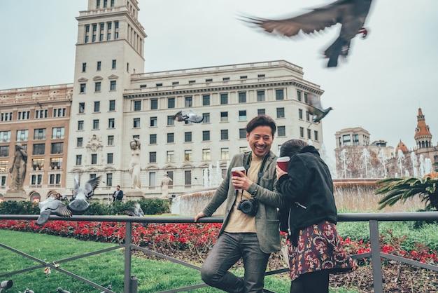 Азиатская туристическая пара смеется над голубями