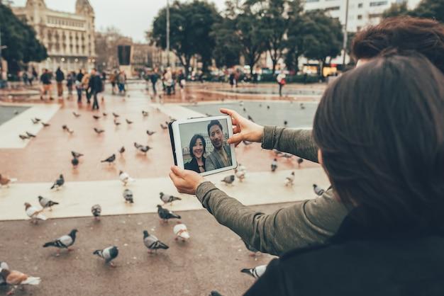 Азиатская туристическая пара, принимая селфи на планшете
