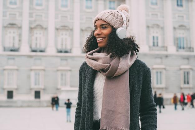 音楽を聴くと冬の王宮近くの携帯電話で踊る若い黒人女性