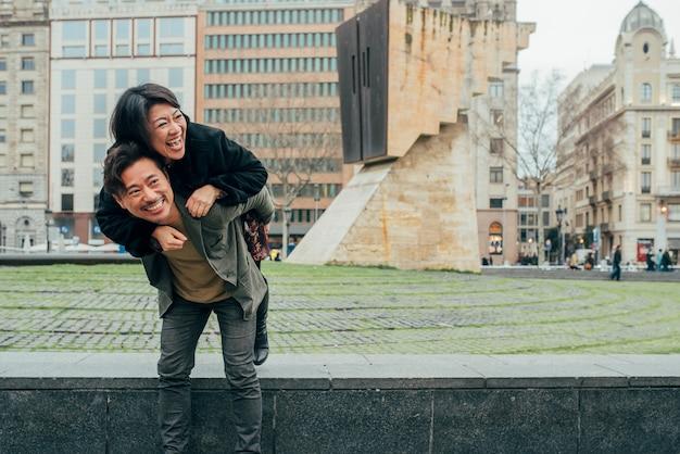 おんぶをしているアジアの幸せな観光客のカップル