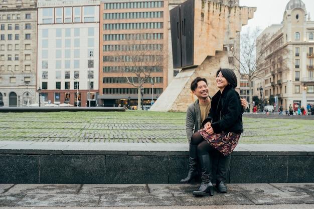 Азиатская пара счастлива турист, сидя на коленях