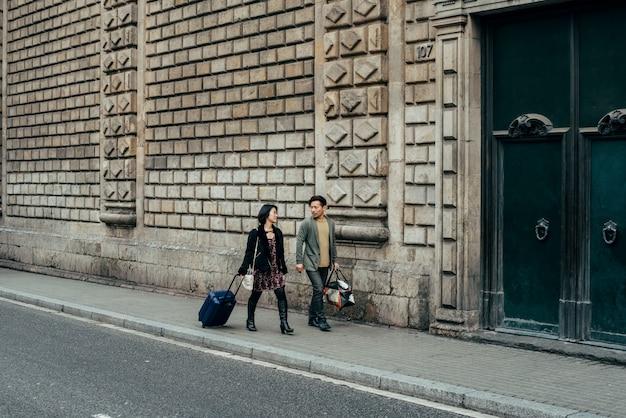 スーツケースを持って歩くアジアの幸せな観光客のカップル