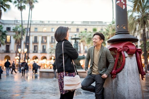 広場で話しているアジアの幸せな観光客のカップル