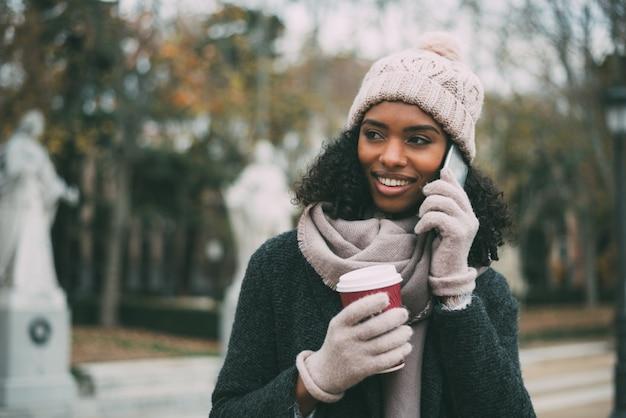 コーヒーを飲むと、冬の王宮近くの携帯電話で話す若い黒人女性