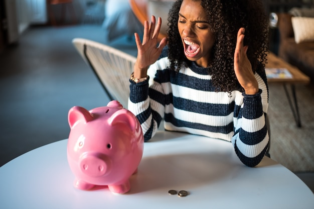 貯金箱で怒っている黒の不幸な女性