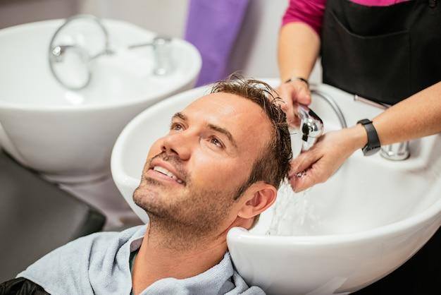 Мужчина моет волосы в парикмахерской