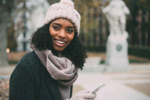 冬の王宮近くの携帯電話で若い黒人女性
