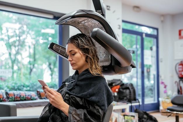 プロの美容師の赤外線ヘアードライヤーの女性