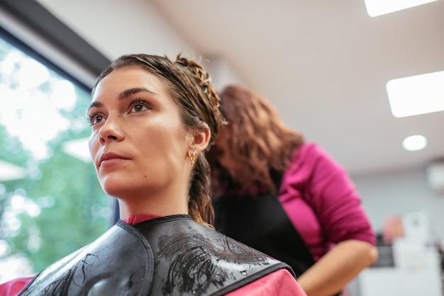 女性の髪をとかす美容院