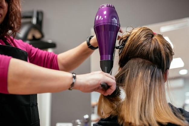 女性の髪を乾かす美容師