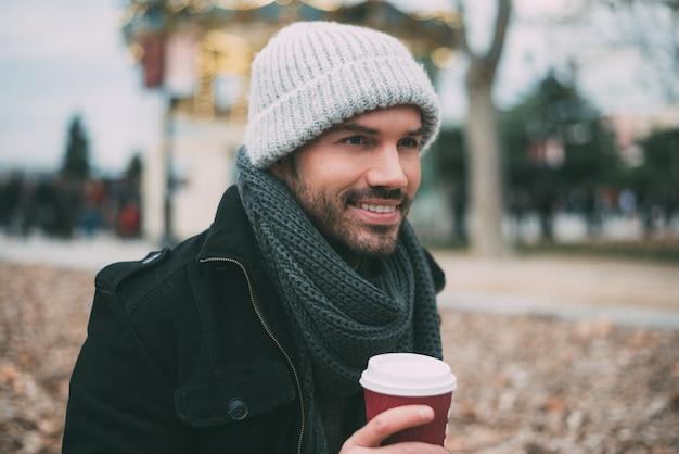 冬の王宮近くのコーヒーを飲む若い金髪男