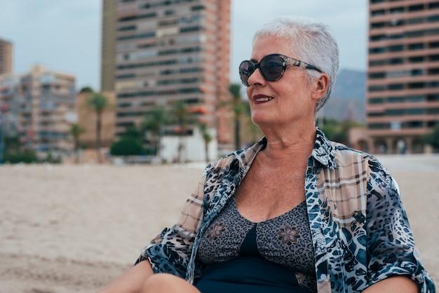 サングラスを着てビーチでシニア老人女性、ビーチに座っている灰色の髪