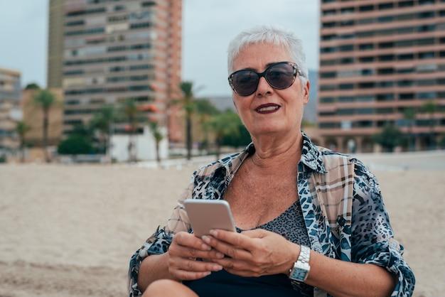 携帯電話でビーチで高齢者の女性