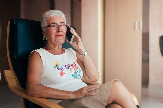 自宅で携帯電話上の高齢者の女性
