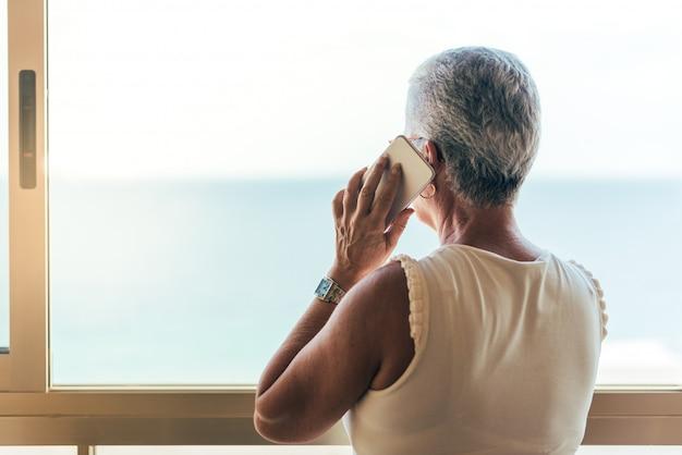 Пожилая женщина на мобильном телефоне дома